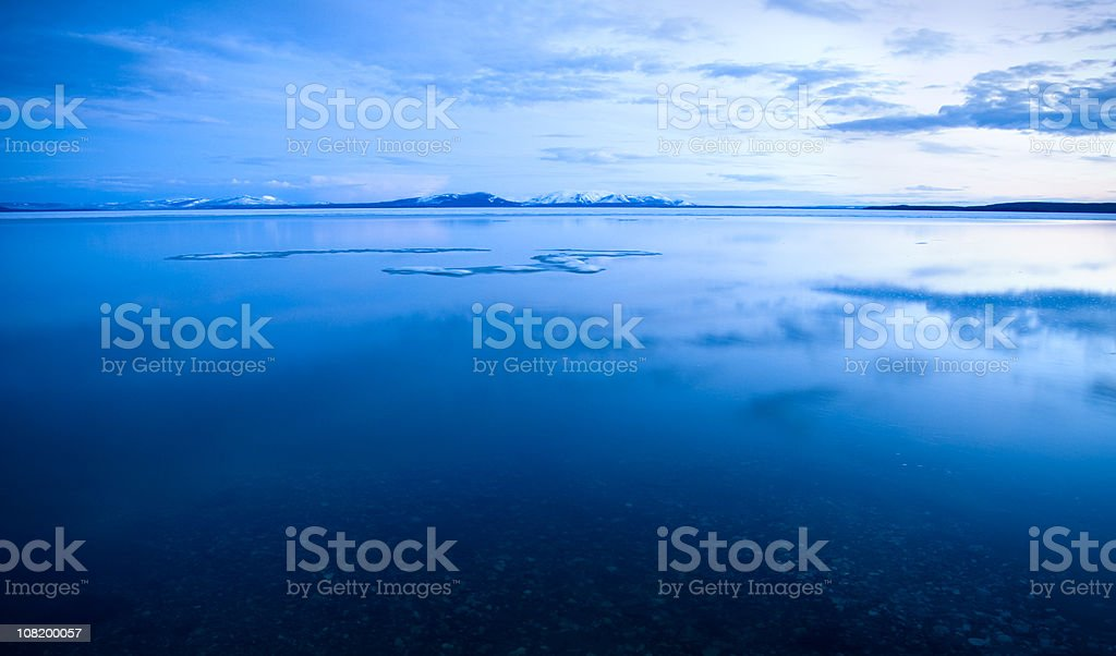 Mountain Lake with Cloud Reflection and Melting Ice royalty-free stock photo