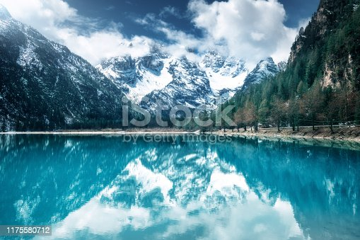 1034754000istockphoto Mountain lake with perfect reflection at sunny day in autumn. Dolomites, Italy. Beautiful landscape with azure water, trees, snowy mountains in clouds, blue sky in fall.  Snow covered rocks. Nature 1175580712