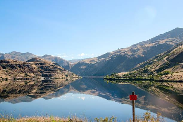 Lago de montanha com reflexos e sinal de perigo - foto de acervo