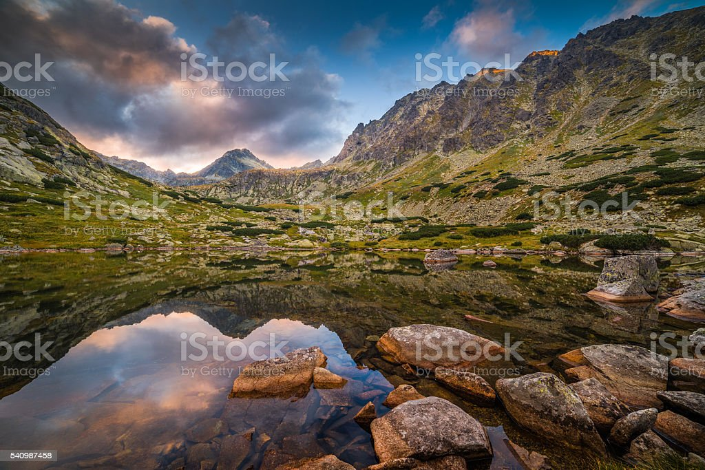 Mountain Lake with Rocks in Foreground at Sunset stock photo