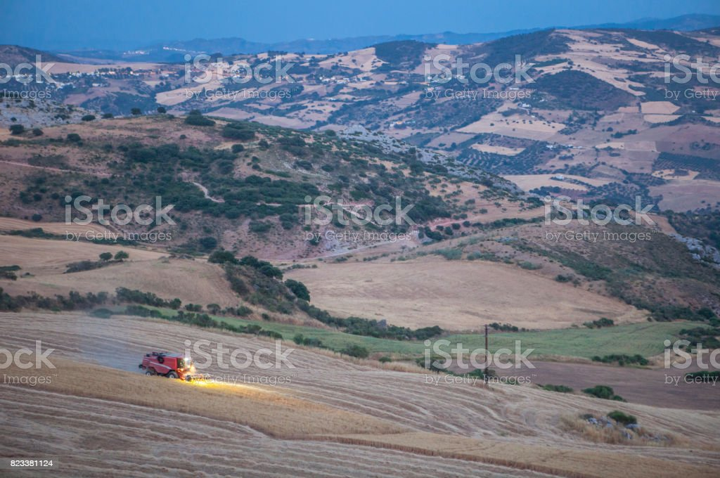 Mountain landscape at dusk with combine harvester working stock photo