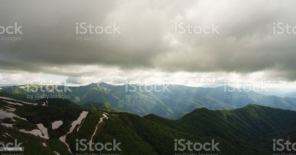 Mountain landscape. Light rays pierces way through the gloomy clouds stock photo