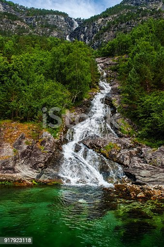 Mountain landscape with a beautiful waterfall and cloudy sky . The beautiful nature of the Norwegian fjords..