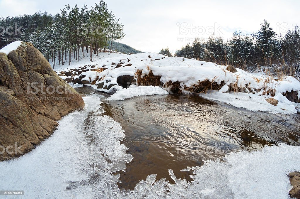 Mountain landscape with a frozen creek stock photo