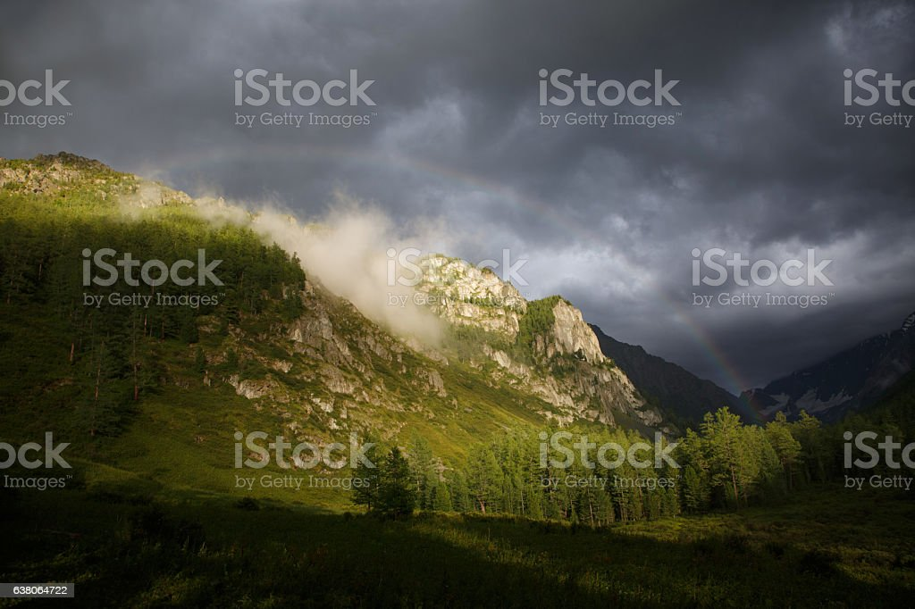 Mountain landscape with a rainbow, clouds and mountain lit by – Foto