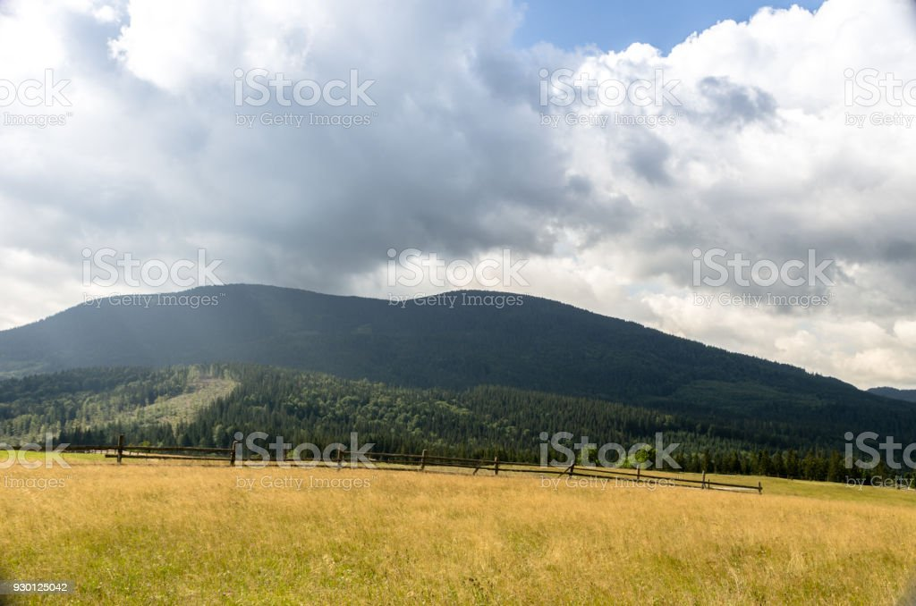 Mountain landscape with mountains and field. Wooden rural fence. stock photo