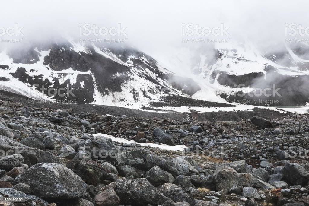Mountain landscape with rocks and creeping fog. High snow peaks in...