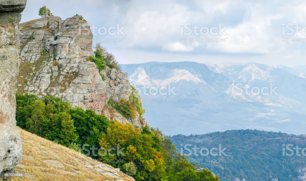 Mountain landscape with weathered rocks and autumn forest on a...