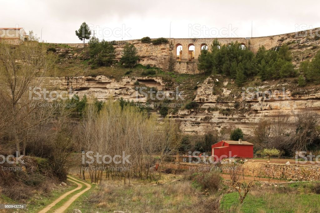 Mountain landscape with wooden house and view of old stone aqueduct stock photo