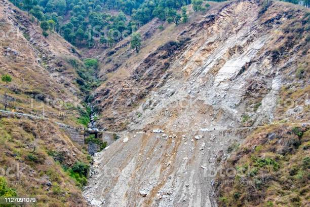 Photo of Mountain landslide in an environmentally hazardous area blocking road.