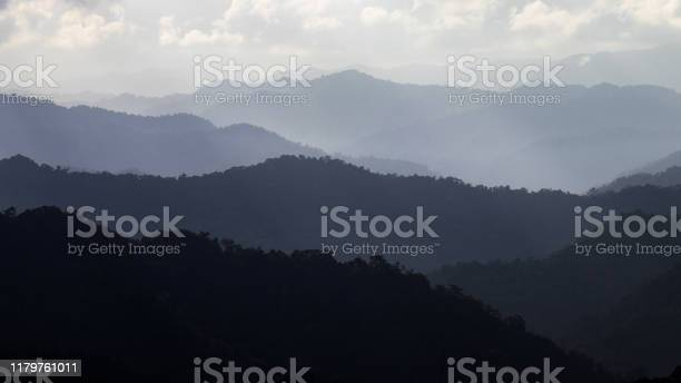 Photo of Mountain layers in morning sun ray with winter fog.