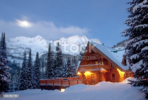 A winter scenic of a rustic, timber-framed lodge in the Canadian backcountry. Horizontal colour image. British Columbia, Canada. Rocky Mountains. Image taken at night with log cabin structure lit with moonlight and starlight.