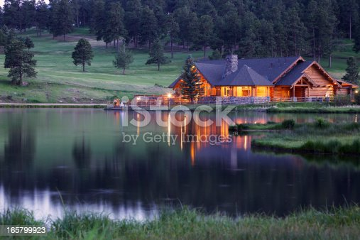 Mountain Lodge in Evergreen Colorado Reflecting in Lake at Dusk. This lodge is part of the public park area.