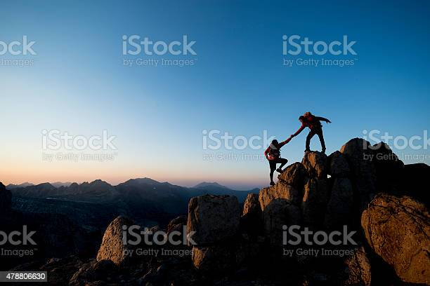 Two mountain climbers helping one another to the summit