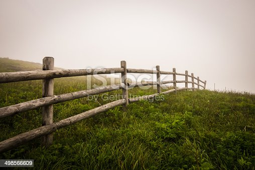 Along the Appalachian Trail, a fence seems to go on forever in to the fog.
