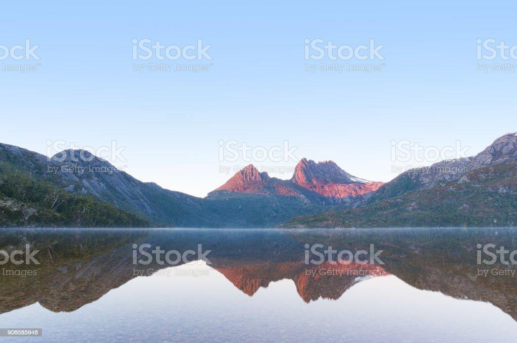 Mountain on sunrise reflected on mirror like lake water stock photo