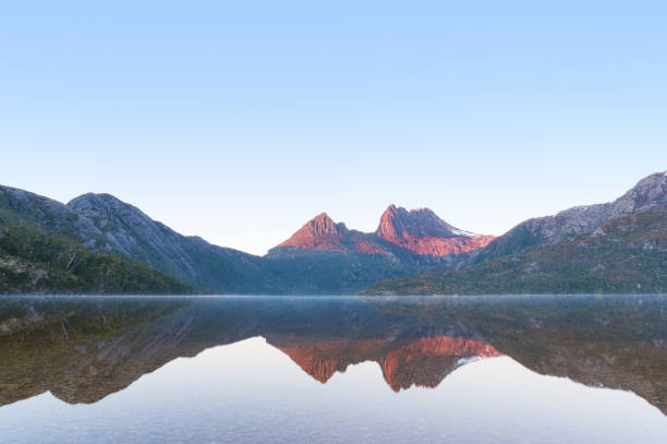 mountain on sunrise reflected on mirror like lake water - cradle mountain stock photos and pictures