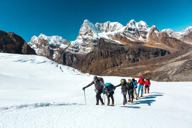 Bergpanorama-Ansicht und Kletterer, die auf Snow Terrain hinauflaufen – Foto