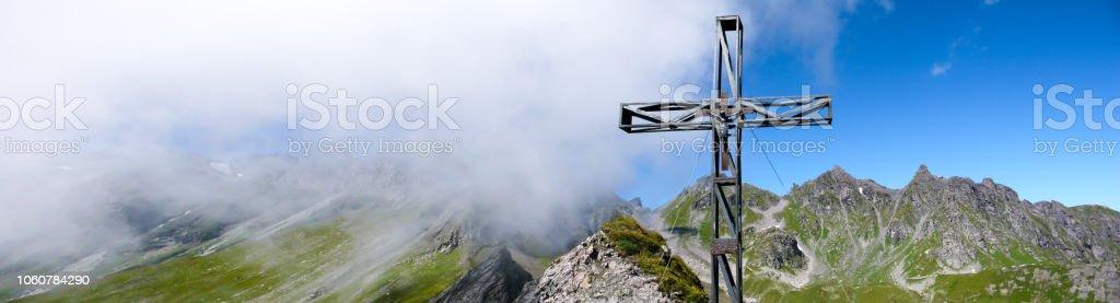 Bergpanorama mit einem wunderschönen Blick auf die Schweizer Alpen und Täler und Metall Gipfelkreuz – Foto