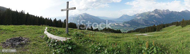A mountain panorama with a gorgeous view of the Swiss Alps and Valleys and a summit cross