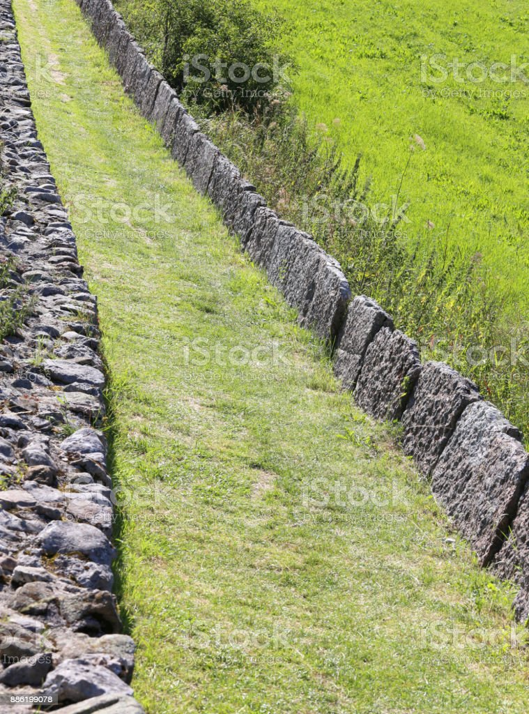 mountain path bordered by stone blocks stock photo