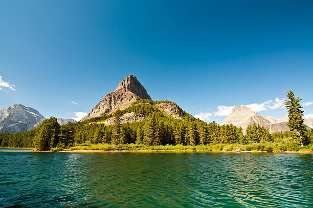 mountain peak by blue water - mcdonald lake stock pictures, royalty-free photos & images
