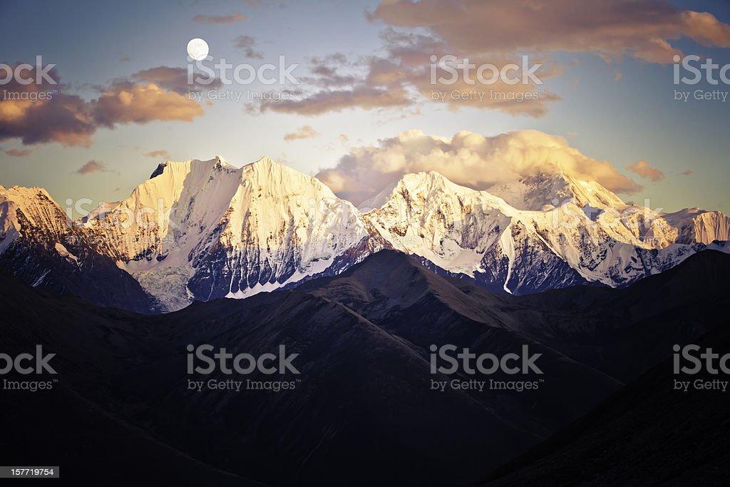 Mountain peak in sunset with moonrise stock photo