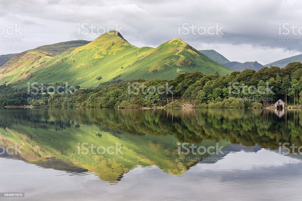 Mountain Peak Reflections In Derwentwater Lake. A scenic view of one the Lake District's favourite views at Derwentwater, Keswick. The image features Catbells mountain, reflected in calm still water. Backgrounds Stock Photo