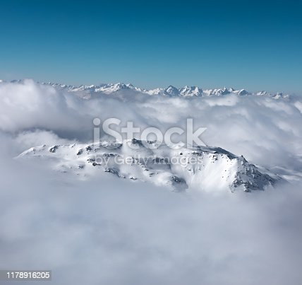 Snowcapped mountain peaks looking out through the fog.