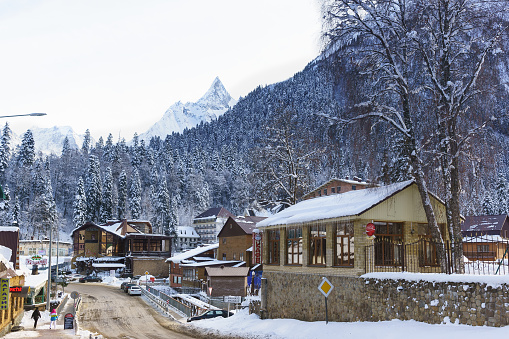 mountain peaks rise above Karachay Street and the bridge over the Amanauz river in the resort village. Winter day