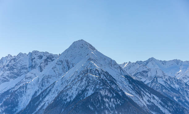 Mountain peaks textured and covered in melting snow - mountin ridges covered in snow stock photo