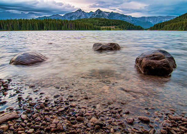 Mountain Peaks with Three Rocks in Lake stock photo