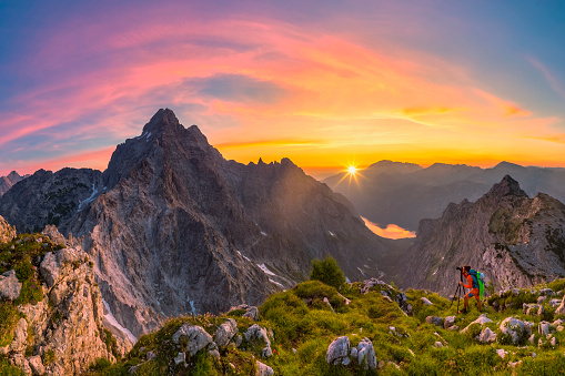 Mountain Photographer at glory sunrise with view to Watzmann and summit Cross of Mount Großer Hundstod
