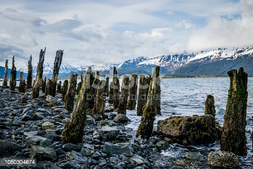 Rotten wood posts from ancient wharf with mountain range and cloudy sky in background. Seward in the Kenai Fjords National Park, Alaska