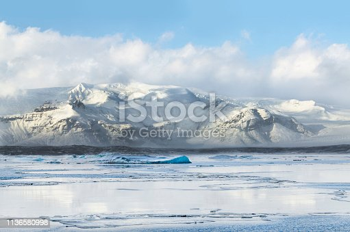 Mountain range, a part of Vatnajokull as background to Jokulsarlon lake with ice floes