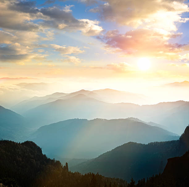 mountain range with sun setting in background - atmospheric mood stock photos and pictures