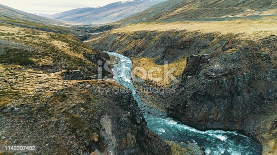 Aerial view of turquoise river winding among rocks