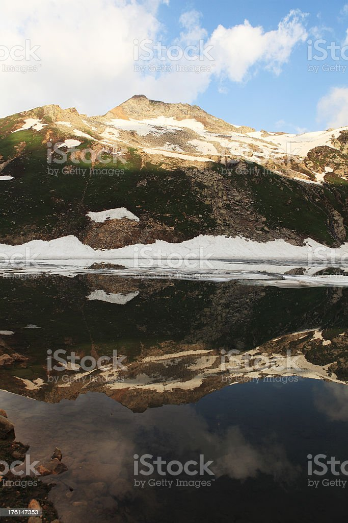 Mountain reflects in half Frozen Ratti Nar Lake, Kashmir royalty-free stock photo