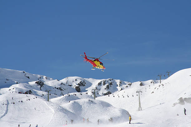 Mountain rescue helicopter flying over the snow to aid stock photo