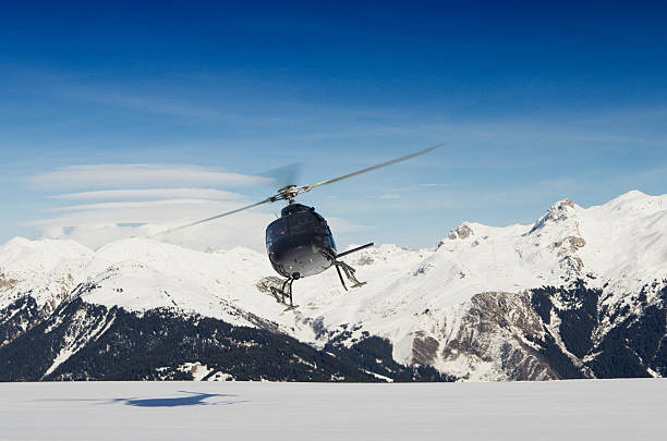 A mountain rescue helicopter in flight by snowy mountains stock photo