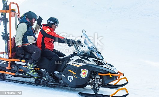 Bulgaria. Bansko. 12 February 2019.lifeguard man riding a snowmobile in the mountains. Medical worker to help the injured