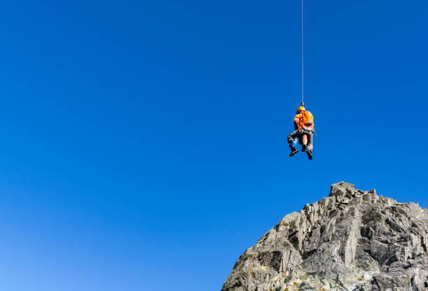 Ein Bergretter und ein verletzter Tourist wurden aus den Bergen gebracht und mit einem Seil per Hubschrauber in die Stadt transportiert. – Foto