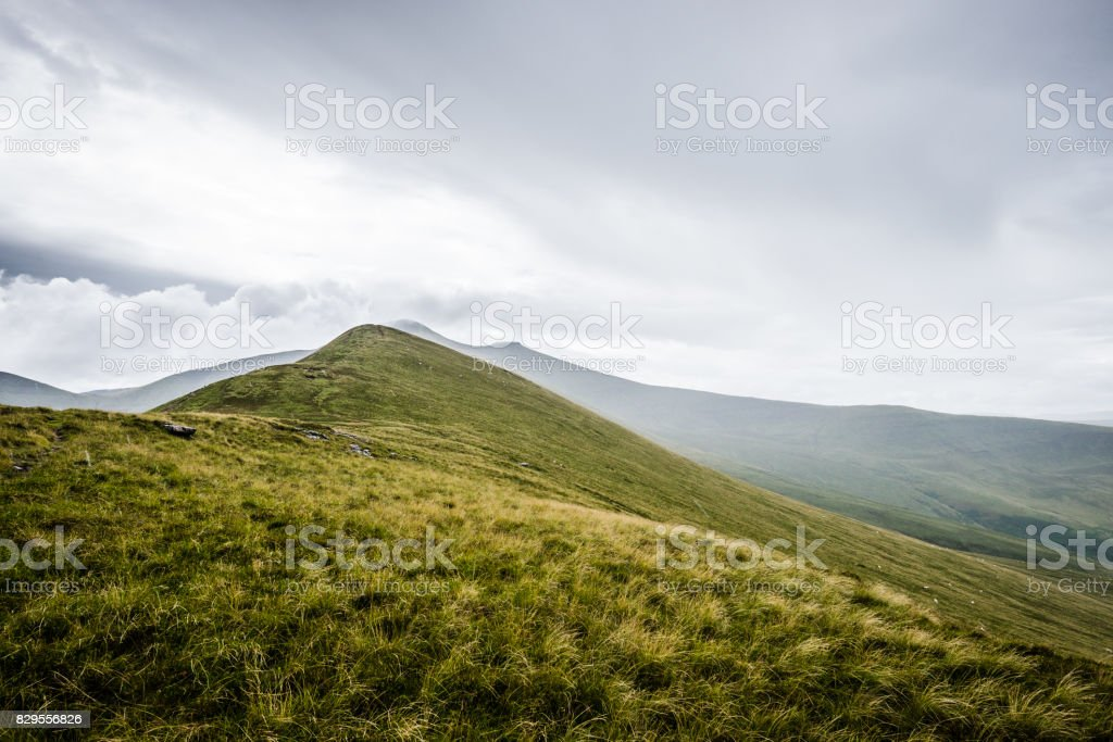 Mountain ridge and moody sky after rain on ascent to Pen y Fan mountain, Wales, Brecon Beacons National Park stock photo