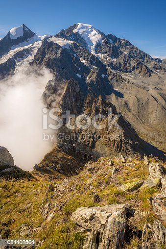 A hiking trail along a steep mountain ridge above glacier valleys with rivers and waterfalls.