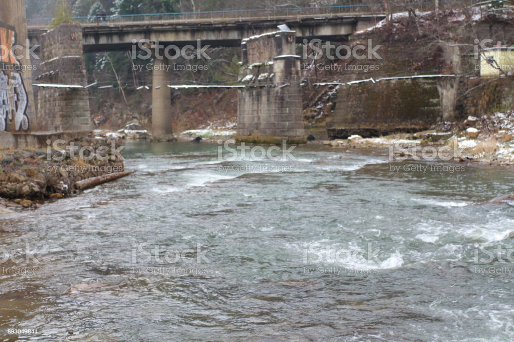 mountain river flows through a bridge stock photo