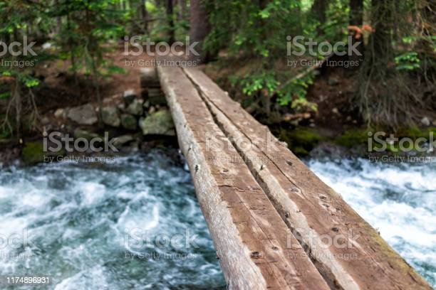 Photo of Mountain river stream in rocky mountains in summer of 2019 on Conundrum Creek trail in Aspen, Colorado with wooden bridge