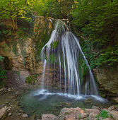 Mountain River with, forest landscape. Tranquil waterfall scenery in the middle of green forest. Beautiful Crimean waterfall Dzhur-dzhur