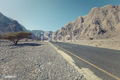 lonely empty road through the al hajar mountains in musandam peninsula, sultanate of oman.
