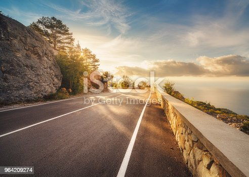 Mountain road at sunset in Europe. Landscape with rocks, sunny sky with clouds and beautiful asphalt road in the evening in summer. Colorful travel background. Highway in mountains. Transportation