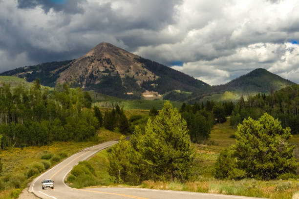 Mountain road before a storm View of a road between mountain peaks in Colorado, USA; stormy clouds about the peaks; one car driving steamboat springs stock pictures, royalty-free photos & images